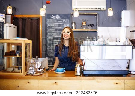 The Girl Adds Milk To The Cup With Coffee In Cafe. Young Woman Barista Working In Coffee Shop