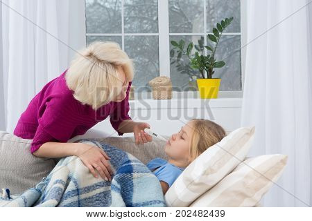 Mother measuring temperature of her sick child. Worried mom checking temperature of her daughter.