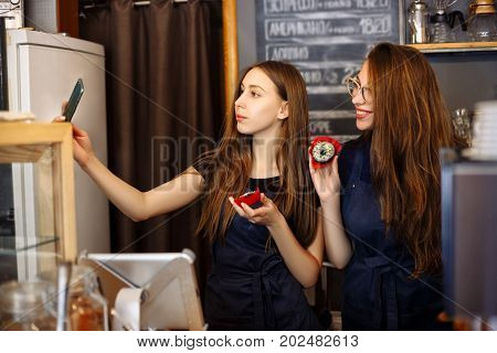 Two Happy Girls Baristas Holding Donuts In Their Hands And Making Selfies