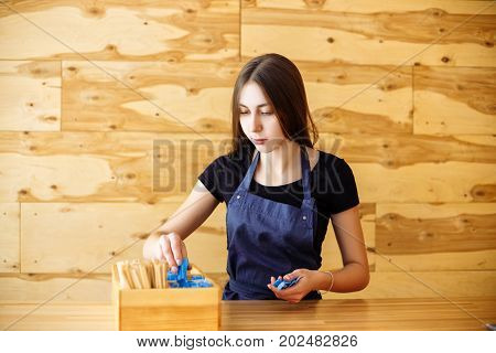 Cute Barista Girl Piles Stick With Sugar Standing In A Coffee House