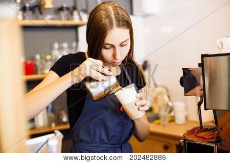 Pretty Barista Pouring Milk Into Cup Of Coffee At The Coffee Shop