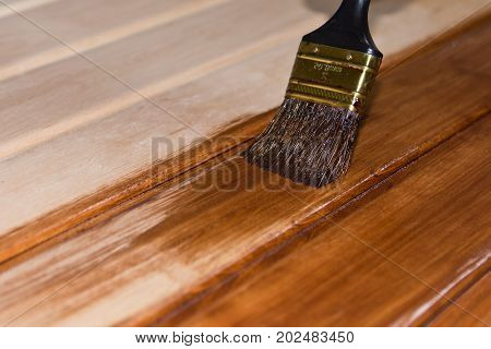Painting a wooden surface with brushes and paint copy space .