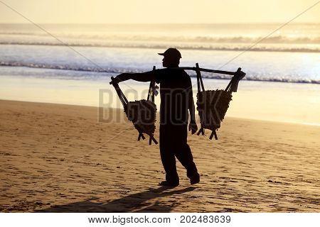 Bali Indonesia - 22 February 2012: Speanut seller on the beach at sunset. Bali Indonesia