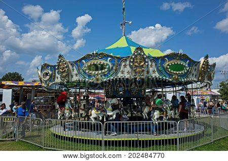 ELIZABETHTOWN, PA, USA-AUGUST 26, 2017: Carousel at small town carnival and country fair. Fairs showcase local talent, agricultural heritage, and provide all types of food for fair visitors.