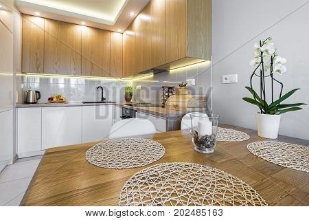 Modern kitchen interior design with wooden table and cupboard doors.