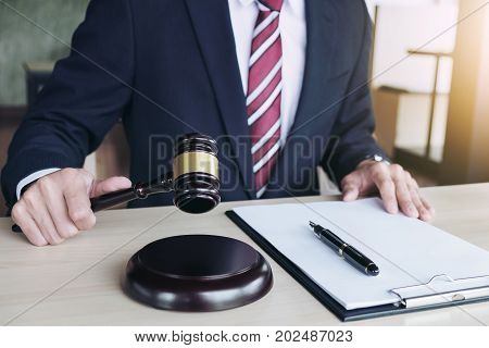 Close up of hand Judge hitting gavel and scales of justice Report the case with note paper on wooden table Law and justice concept.