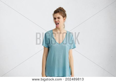 Irritated Young Woman With Grumpy Expression, Showing Tongue While Being Dissatisfied With Something