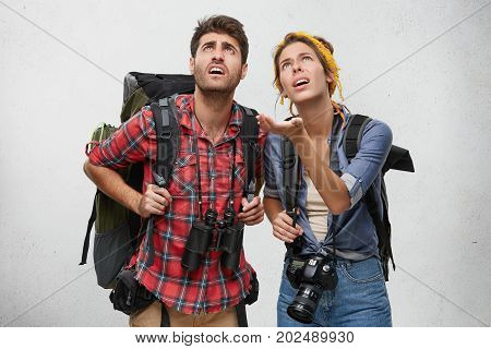 Just Look At This! Astonished Female With Rucksack And Camera Showing Something With Hand To Her Hus