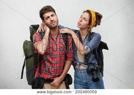 Attractive Young European Female With Photo Camera Massaging Neck Of Her Frustrated Sick Boyfriend W