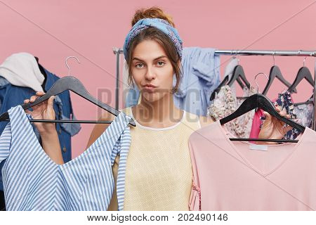 Attractive Young Caucasian Woman Customer Holding Hangers With Two Pieces Of Clothing, Feeling Doubt