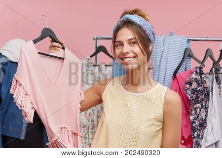 Attractive Female Fashion Designer Holding Hanger With Stylish Pink Top While Presenting New Summer