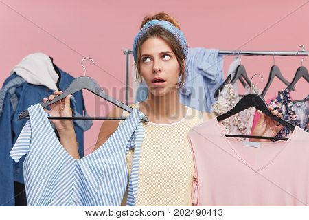 Beautiful Woman With Tired Expression Holding Two Hangers With Dresses Choosing Between Two. Discont