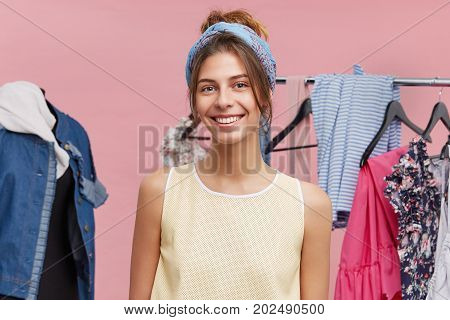 Pretty Teenage Girl In Good Mood Doing Spring Cleanup In Her Wardrobe, Standing At Rack With Hangers