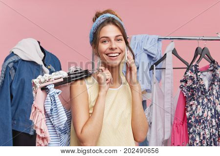 Happy Smiling Woman Standing In Boutique With Clothes, Telephoning Her Friend, Telling Her About Suc