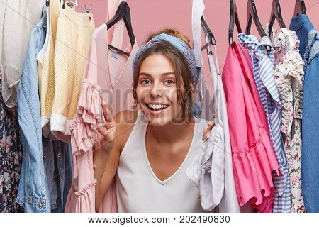 Beautiful Female With Happy Expression Looking Through Her Clothes, Being Glad To Choose Outfit By H