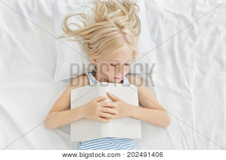 Top Shot Of Adorable Little Female Child Napping In Bed. Cute Baby Girl With Freckles And Blonde Hai