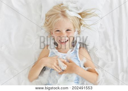 Funny Small Child With Light Hair, Lying On White Bedclothes, Feeling Joy While Catching Feathers, H