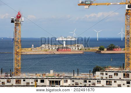 Copenhagen, Denmark - July 16 2013: Construction and tower cranes against the background of the Trekroner fortress, wind turbines and liner