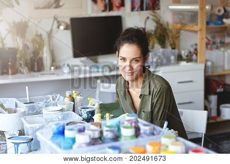 Indoor Shot Of Creative Female Painter With Beautiful Appearance Sitting At Table Surrounded With Co