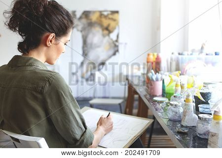 Rear View Of Brunette Young Caucasian Woman Artist In Khaki Shirt Holding Pencil, Sketching At Works