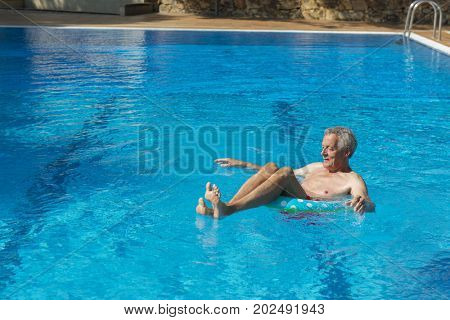 Vacation by senior man playing in swimming pool