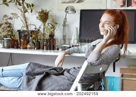 Picture Of Confident Carefree Young European Woman Artist Relaxing On Chair In Modern Studio, Smilin