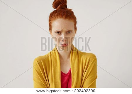 Unhappy Upset Red-haired Teenage Girl With Hair Knot Having Offended And Dissapointed Look, Pouting