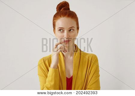 Portrait Of Stunning Young Female Wearing Her Ginger Hair In Knot Touching Lips, Looking Away With S