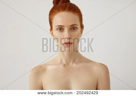 Horizontal Portrait Of Naked Beautiful Female With Freckled Healthy Skin And Ginger Hair Tied In Kno