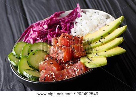 Marinated Tuna Poke Bowl With Rice, Fresh Cucumbers, Red Cabbage And Avocado Close-up. Horizontal