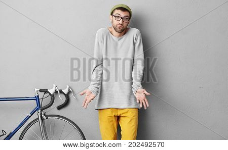 Stylish Young Cyclist In Trendy Clothes, Having Beard, Shrugging His Shoulders With Uncertainty, Not