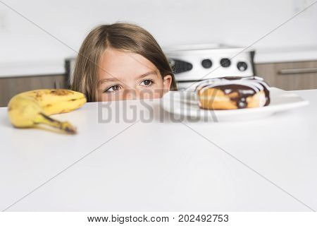 A kid choosing between healthy vegetables and tasty sweets