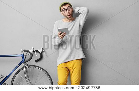 Young Male In Fashionable Clothes, Staring At Camera While Doing Online Shopping, Using Tablet, Bein