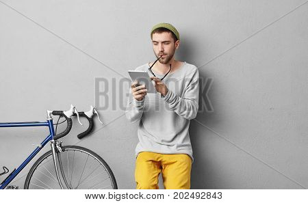 Indoor Portrait Of Handsome Male Student Reading Attentively Lecture On Modern Tablet, Taking Off Gl