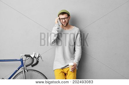 Indoor Shot Of Tired Man With Attractive Appearance, Keeping His Hand Near Head, Having Headache Aft