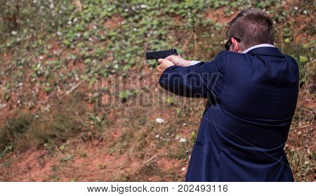 A businessman holding a pistol and aiming at an enemy wants to destroy the attackers by shooting them from a gun