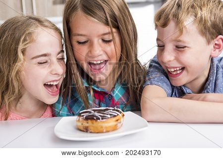 three Young child Sitting At Table watch Donut