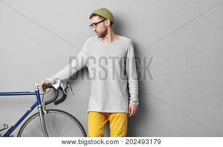 Young Hipster Guy In Loose Sweater And Glasses Choosing Bicycle For Himself, Wanting To Exercise Eve