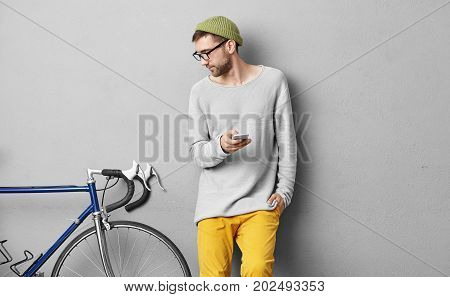 Serious Unshaven Young Man In Trendy Wear Posing At Concrete Wall And Looking At His Fixed Gear Bike