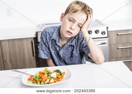 lovely boy showing boring expression with fresh colorful vegetables