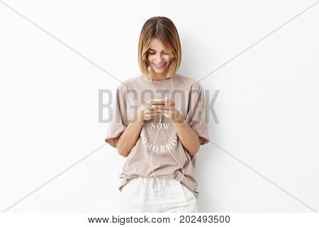 Horizontal Portrait Of Happy Smiling Female With Bobbed Hairstyle Dressed Casually Being Happy To Re