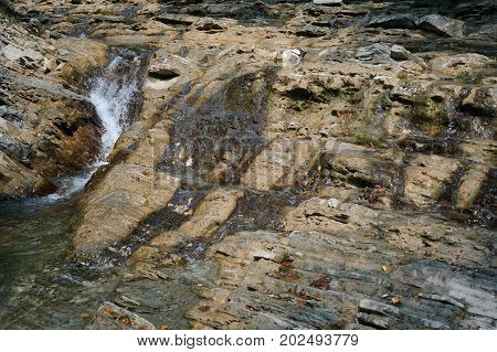 Water flows over the rock. Small waterfall on the rocks. Natural background
