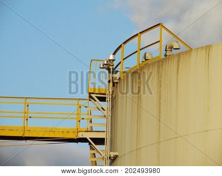 A cross-section of a white/gray oil tank with a yellow guardrail and yellow metal bridge.