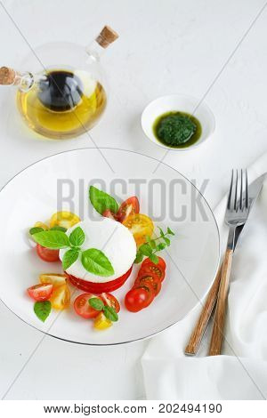Caprese salad with ripe cherry tomatoes and mozzarella cheese with fresh basil leaves isolated on the white background. Top view..