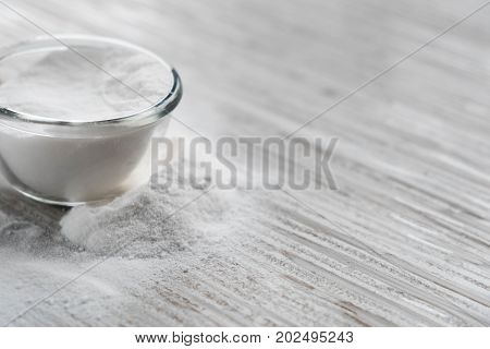 Glass bowl of baking soda. Spoonful of bicarbonate. Baking soda Sodium bicarbonate NaHCO3