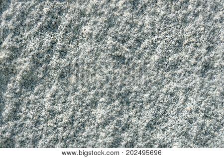 Natural stone grey granite background. Bright hard grey granite rock texture. Grey granite stone background. Grey granite untreated surface. Facing granite material full frame horizontal texture. Gray granite texture background. Natural rock gray granite