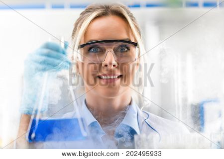Happy young attractive excited smiling female scientist holding a flask with blue liquid substance in the clouds of smoke in the chemical research laboratory