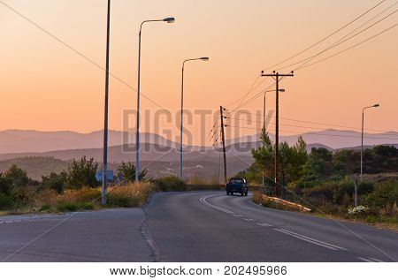 Typical greek coastal road at sunset with one pickup driving by, Sithonia, Greece