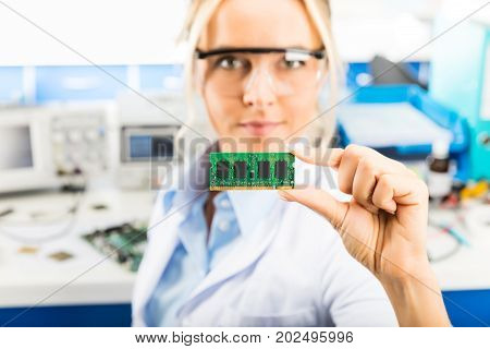 Young attractive smiling female digital computer electronic engineer with protective sunglasses holding laptop or notebook computer DRAM memory module in hand in the laboratory