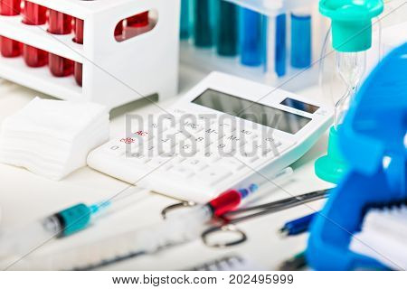 Macro view of the scientific chemical laboratory equipment - calculator, test tubes with color liquid substance samples, vials, flasks, report documents etc. with selective focus effect